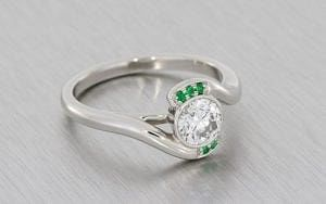 Contemporary Bypass Design Engagement Ring Set With A Round Brilliant Diamond And Framed With Forest Green Emeralds.