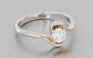 Round brilliant diamond set in a bypass shank with intricate Celtic knot detailing