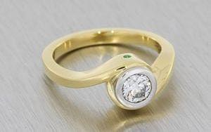 Yellow Gold & Platinum Bezel Set Round Brilliant Crossover Soliatire with emerald and peridot flush set peak stones