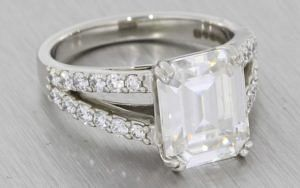 A Dramatic Split Shank Platinum Diamond And Emerald Cut Moissanite Engagement Ring