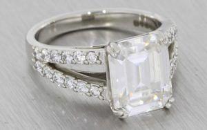 A Dramatic Split Shank Platinum Diamond And Emerald Cut Moissanite Engagement Ring