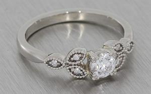 Platinum round diamond ring with diamond shoulder elements