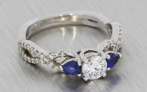 Crossover style palladium engagement ring set with diamonds and sapphires