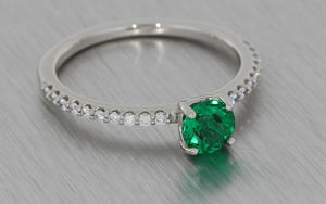 Dainty platinum ring set with a round emerald and diamond shoulders