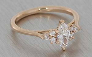 Delicate rose gold engagement ring set with a marquise cut diamond with small round accent diamonds