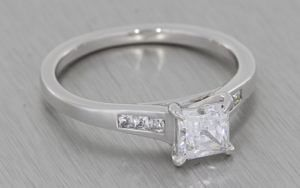 Silver proposal ring set with a square cubic zirconia with smaller squares in the shoulders
